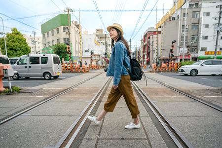 Voyage détendu femme marchant à travers le chemin de fer tenant son téléphone dans la ville d'Osaka au Japon.