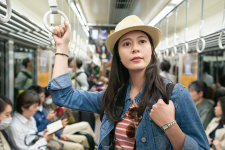 beautiful asian visitor taking the train and holding handrail while heading to the destination in japan 版權商用圖片