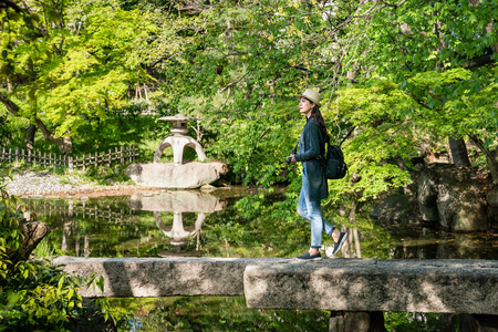 a young travel woman walking on a bridge in the Japanese garden full of beautiful plants and japanese building.