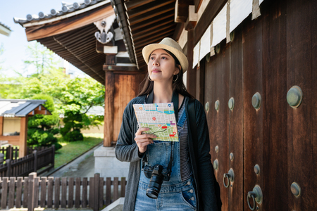 appealing asian traveler visiting the old japanese traditional building with a guidemap.