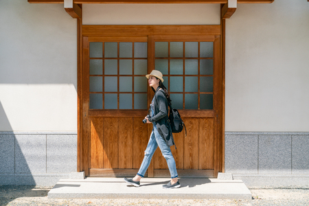 beautiful travel woman passing thru a traditional building and browsing around in osaka