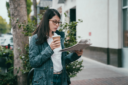 woman reading a newspaper while drink a cup of coffee and ready for her office work.