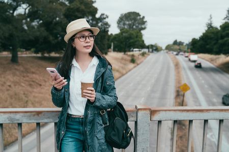 beautiful woman holding coffee and phone and leaning on the guardrail on the bridge joyfully.