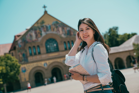 a beautiful asian student holding her books and looking into the camera with a charming smile.