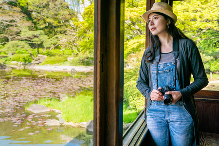 pretty young woman holding a camera and browsing the view thru the window in a japanese garden.