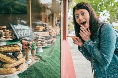 a young girl finding a pastry shop and looking excitingly and pointing to the window ahead of her. Stock Photo