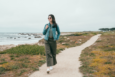 a stylish travel woman walking in a beach path and feeling satisfied by this peaceful place. Stock Photo