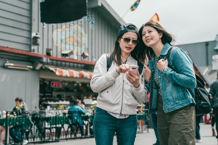 young sisters searching shops by smartphone while visiting a beautiful and old little town.
