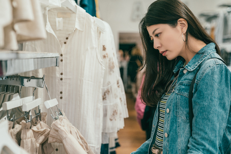 pretty young asian woman browsing and choosing clothes in a ready to wear store. Archivio Fotografico
