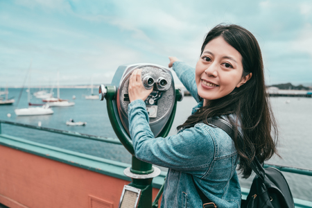 happy attractive girl using a telescope and looking to camera with one hand pointing at somewhere far away.