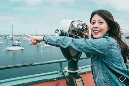 happy beautiful girl pointing at sea while looking through a telescope for finding interesting stuff. Stock Photo