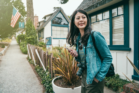 a young happy female standing in front of houses with a cell phone held in one hand. 写真素材
