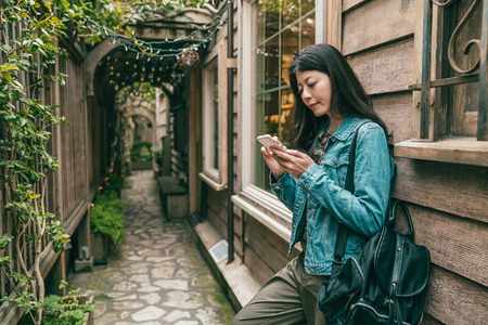 beautiful woman using a smartphone and leaning to an retro building in a alley with plants around.