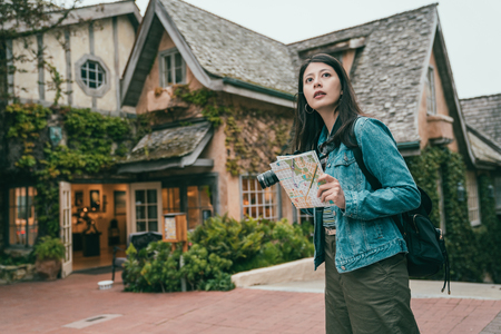 young pretty woman feeling lost while visting a unfamiliar place with a guide book in a lovely and small town. Stock Photo
