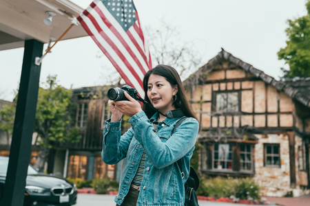 beautiful happy woman taking photos around in a lovely and quiet town whlie visiting here. Stock Photo