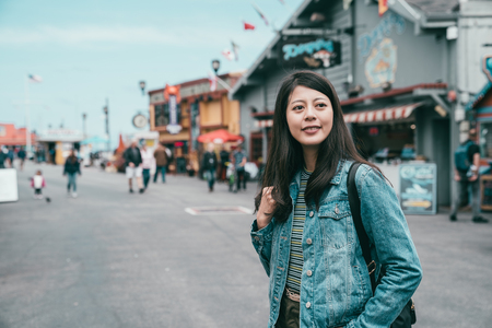 a pretty asian woman visiting a small town and looking joyfully and interested in surroundings. Stock Photo