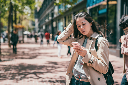 appealing young business woman looking confused and not sure how to reply the message on phone. Stok Fotoğraf