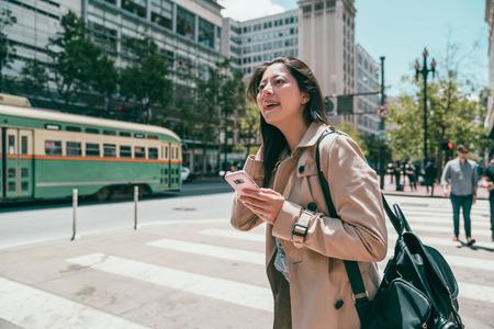 feliz mujer encantadora mirando hacia arriba y sosteniendo un teléfono celular mientras cruza la calle. Foto de archivo