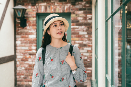 a beautiful woman looking pleasantly and visiting the lovely and retro building in a old small famous town 스톡 콘텐츠