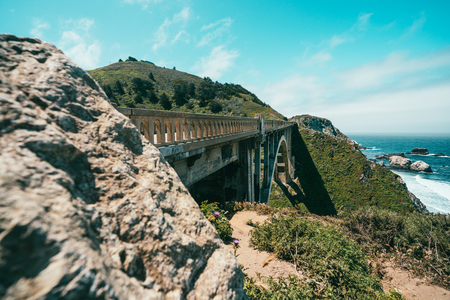 a view from the crag and stunning mountains with a train bridge surrounded by ocean.
