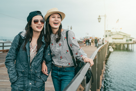 two beautiful good friends having a wonderful time while visiting a beautiful wharf in a lovely day.