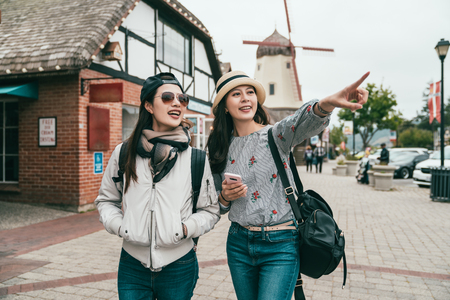 young sisters traveling together in a old town and one is pointing to somewhere ahead joyfully. Фото со стока