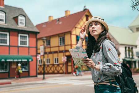 a pretty asina woman having sightseeing with a map while stepping in a lovely and beautiful old town. Stock Photo