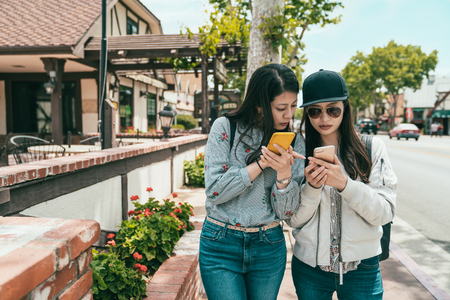 pretty girls discussing something on the phone while walking down the sidewalk in the town.