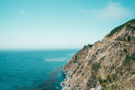 a spectacular scenery of the cliff surrounded by blue ocean and clear sky in nowhere.