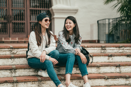 two good friends siiting on the stairs and laughing happily while traveling and hanging out together. Stock Photo