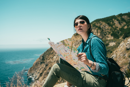 classy girl holding a guide map to view the surrounding while sitting on the cliff for taking a break.