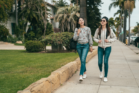 young pretty friends walking on the sidewalk and talking cheerfully while having a relaxing date. Standard-Bild - 108580027