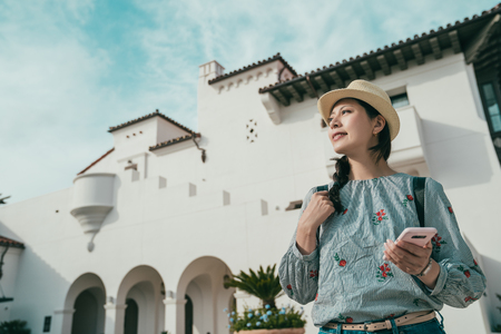 a upward view of a young woman holding a cellphone while visiting a beautiful place in somewhere.
