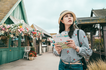 a charming woman holding a guide map and looking lost with a confused look in a old lovely town. Stock Photo
