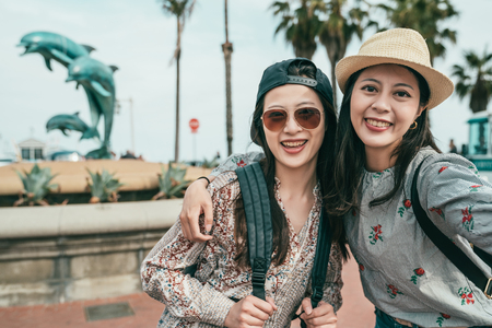 two women smiling and taking selfies happily in front of a dolphin fountain in a lovely plaza.