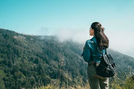 the back view of a woman standing on the cliff with a background of mountains covered with trees and greens. Stock Photo