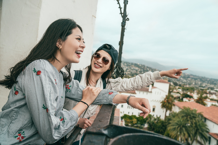 young friends laughing happily and pointing to somewhere on the balcony of an old beautiful house.