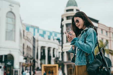 beautiful woman using smartphone to search the location of her favorite bag shop