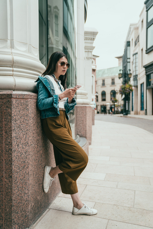 fashion teenager relies on the wall, using her cellphone and waiting for her boyfriend Stock Photo