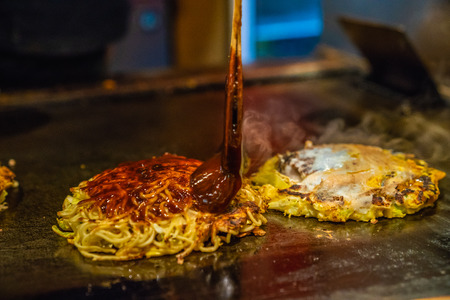 chef is cooking japanese traditional food which is called Okonomiyaki, he is adding spicy sauce in the food