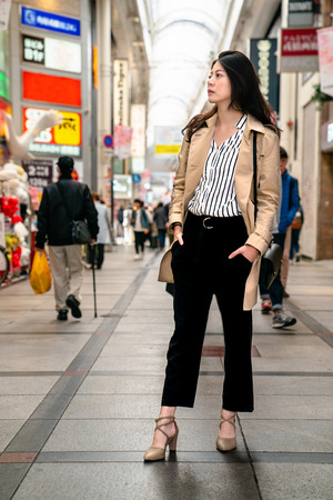 stylish lady standing on the street,  put her hands in the pocket and looking at the shop Stockfoto