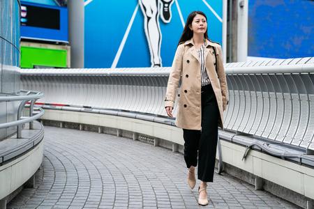 confident businesswoman walking on the footbridge, she is wearing fashion high heels