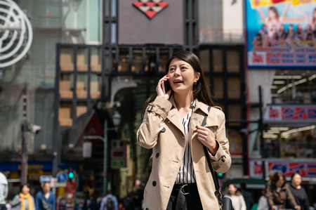 businesswoman waiting her friend on the street and calling her to check when will she arrive