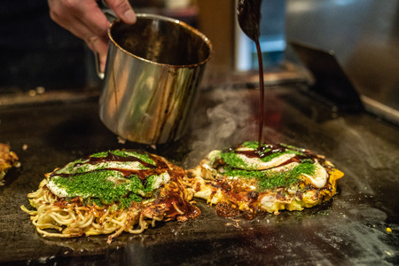 the delicious okonomiyaki is almost done on the iron plate, the cook is adding some japanese traditional sauce