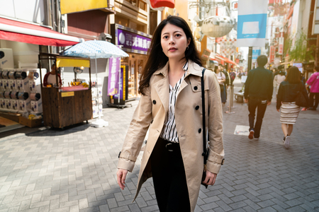 confident lady walking on the street to work, wearing coat and carrying her bag