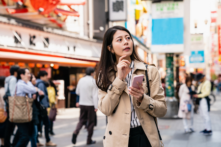 attractive woman finding the right direction by her smartphone