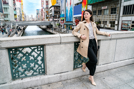 confident office lady wearing a casual suit and standing on the bridge Stock Photo