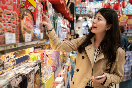 beautiful lady is buying some cookies from the shelf in the local specialty shop in Japan, she found the famous Japanese snack which her friend order her to buy