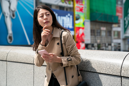 female traveler finding the right direction and looking at the map on the smartphone