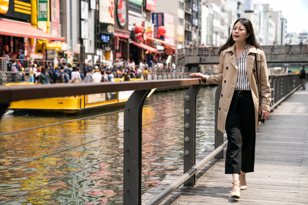 businesswoman relaxing and walking beside the river, she puts her hands on the handrail Archivio Fotografico - 109082939